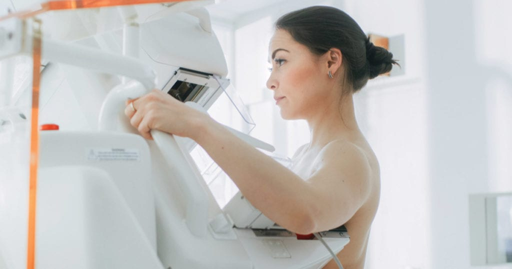 Woman getting her breast scanned in a Mammography machine