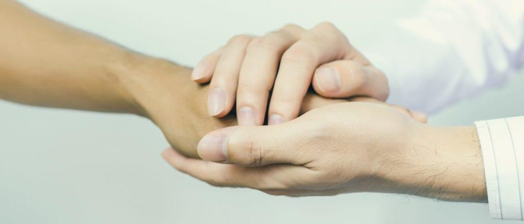 Gentle hands holding a patient hand